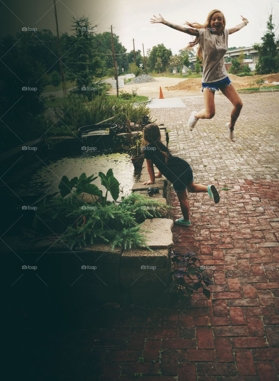 Girl jumping on cobblestone in the village