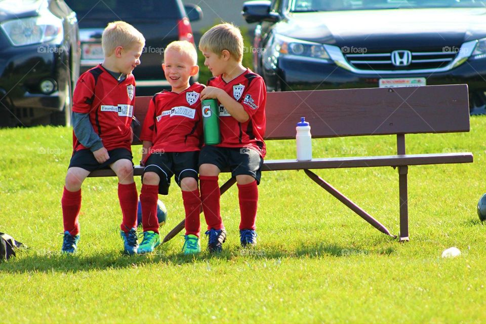 Boys on the Soccer Bench. Three young boys enjoy each other's company on the sideline