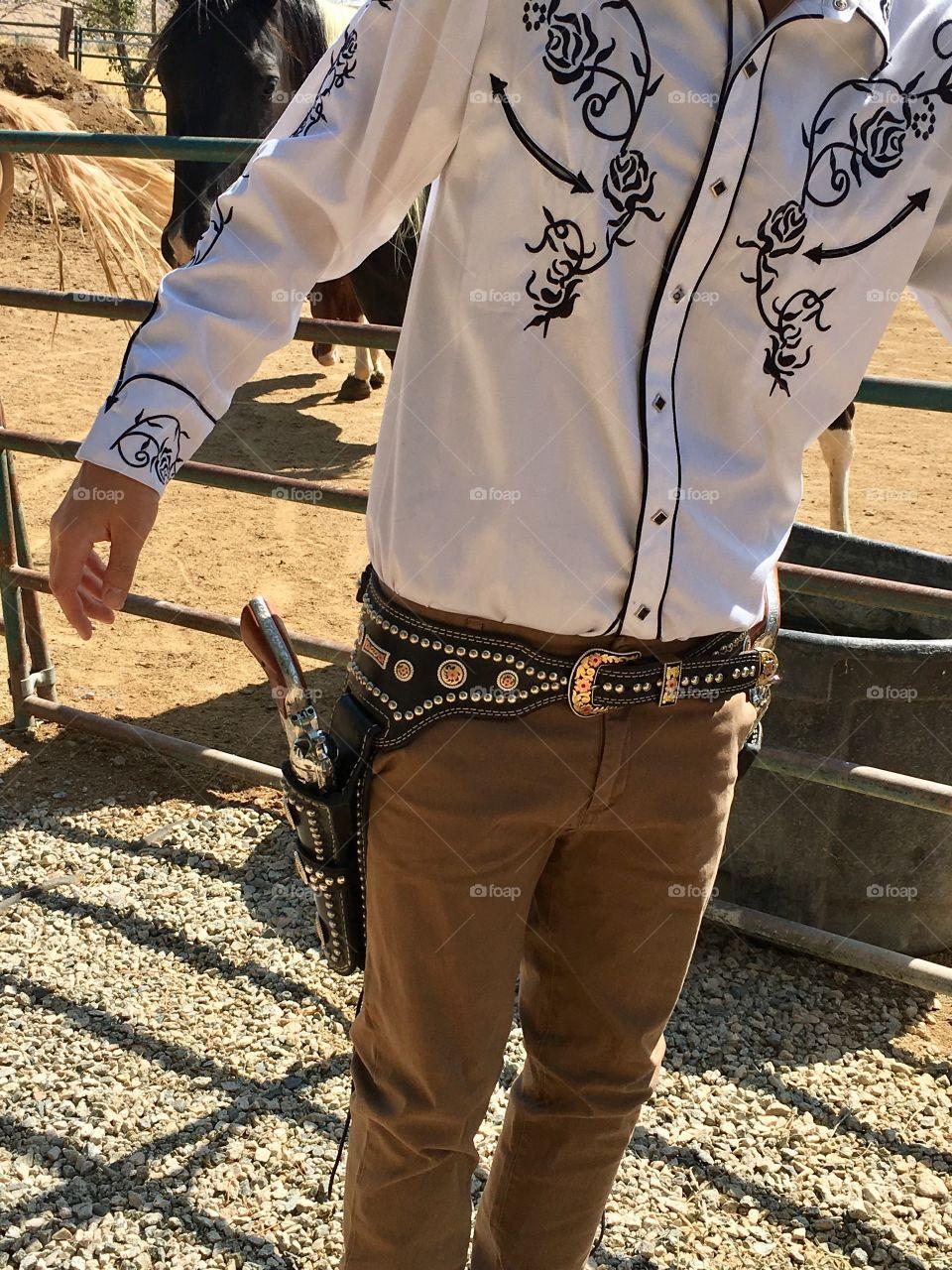 Cowboy wearing western shirt, belt and gun holsters