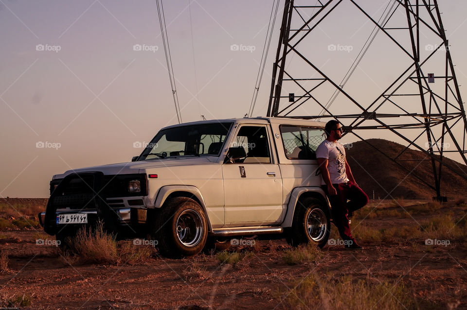 guy and his power. Offroad trip to the desert with a handsome guy and his powerful patrol at sunset. wearing t shirt