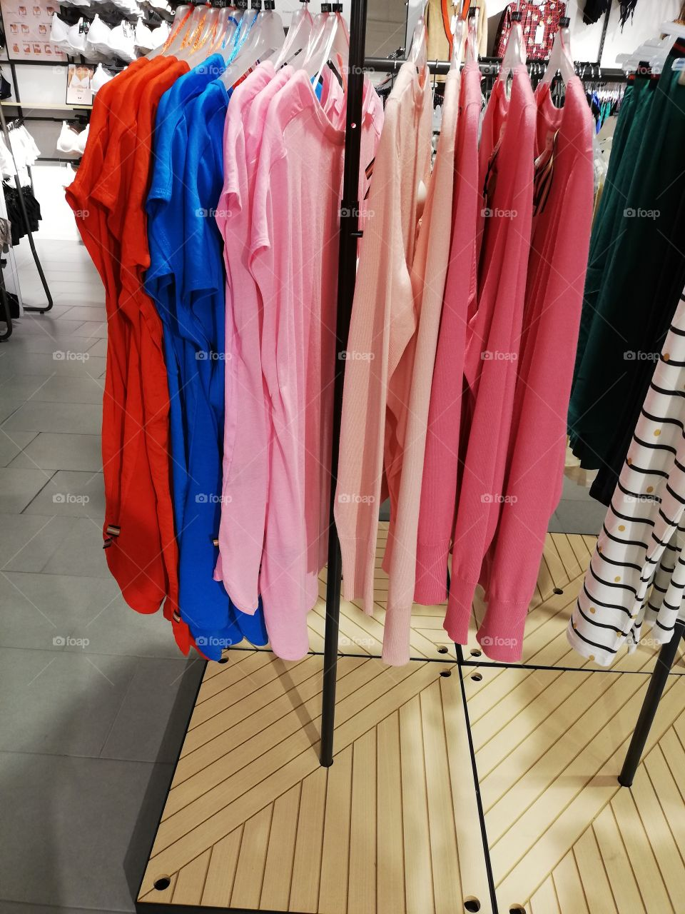 Plenty of different colors nightdresses and striped pants are hanging on the hangers on the rack, sizes are seen above the clothes. In the background white bras are shown in the bright light.