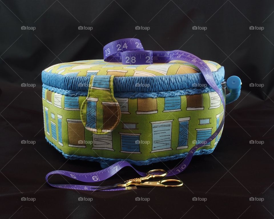 An octagon shaped sewing box with purple measuring tape draped across it and gold handled scissors all with a black background.