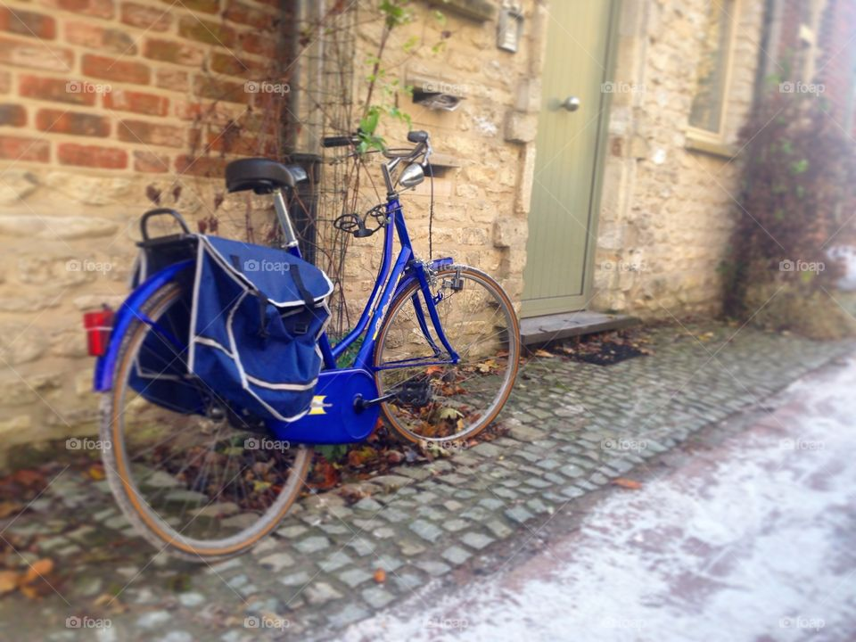 Blue bike in Brussels. A blue bike awaits it's owner's return. The scenery reflects typical Belgian atmosphere- cobblestone and charming homes.