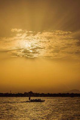 people boat sun sea water river sky sunset