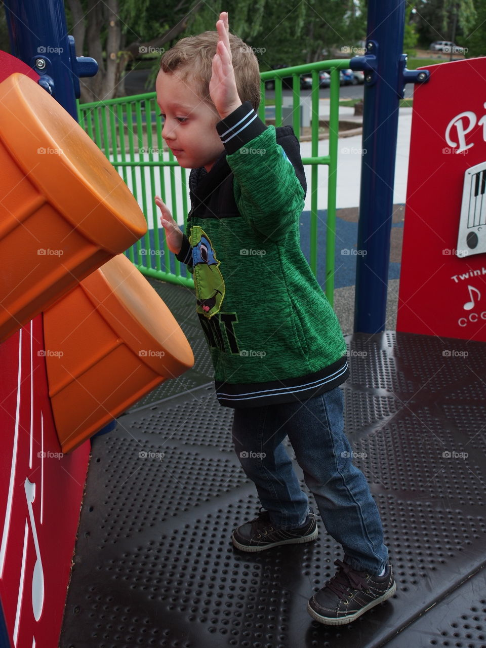 A little boy enthusiastically plays on the plastic drums on a play structure in the park.