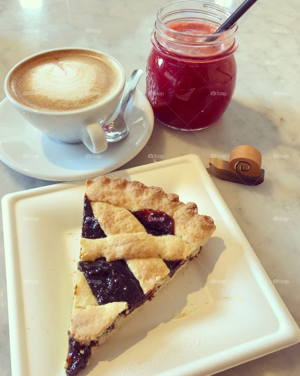 Healthy breakfast time with a cappuccino, prune tart and a centrifuged of red turnips