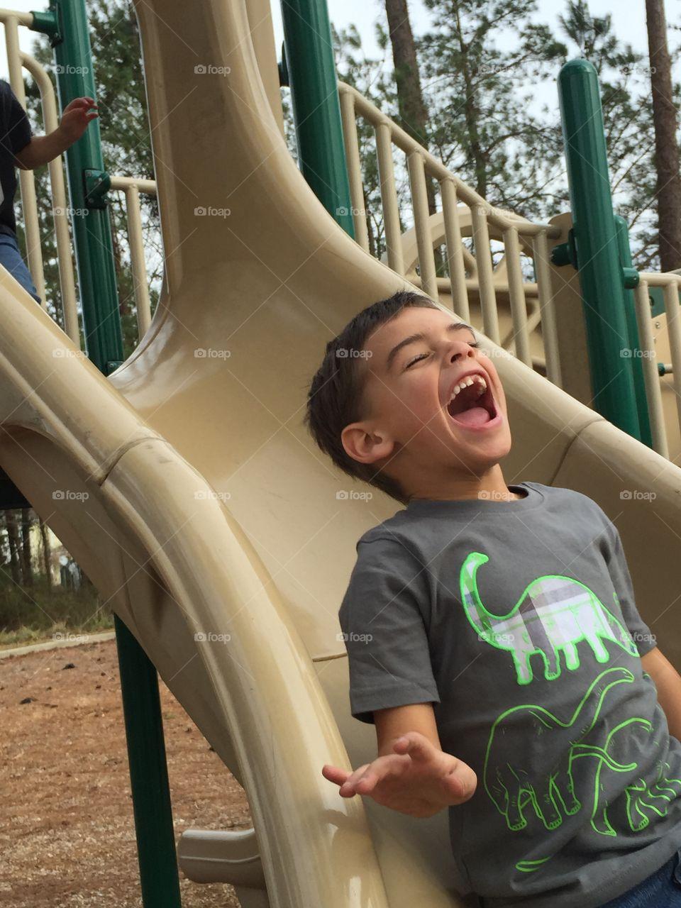 Small child enjoying on slide