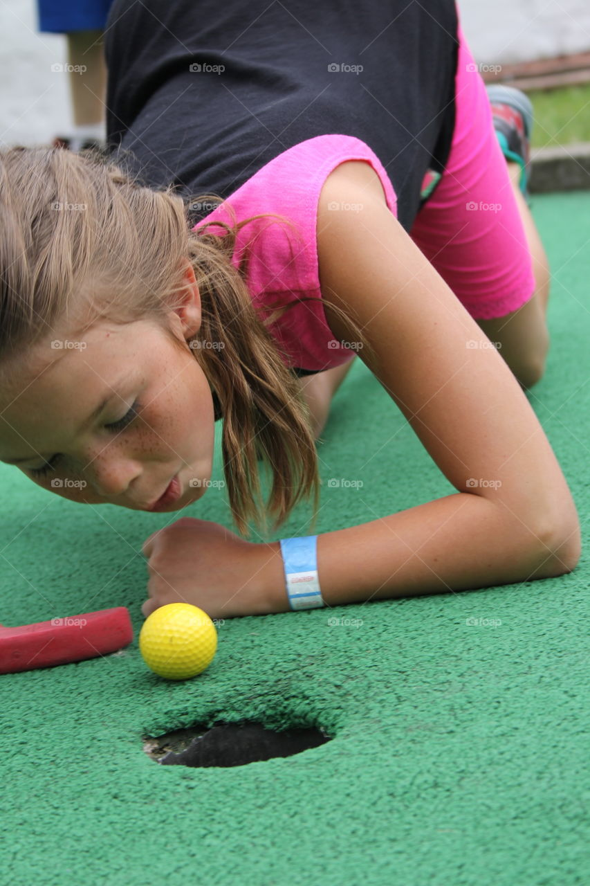 Little girl blowing golf ball in hole