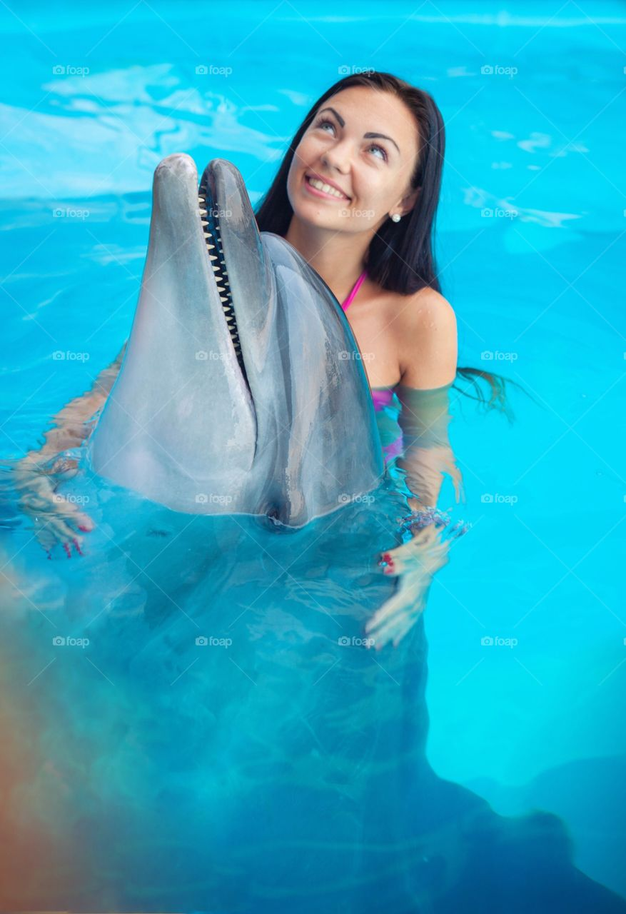 Smiling woman with dolphin in pool