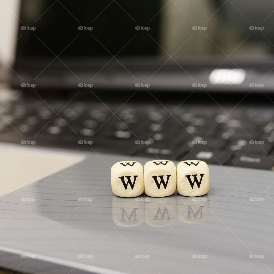 Close-up of www dice with laptop