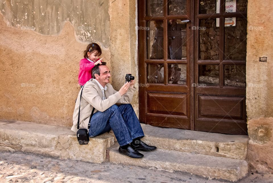 A  little girl with her father taking a photo