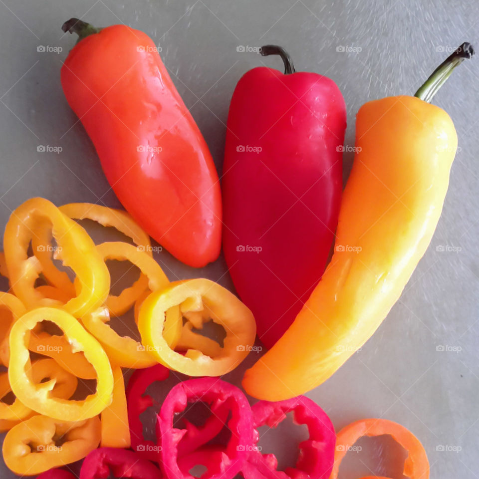 Colorful whole and sliced sweet peppers