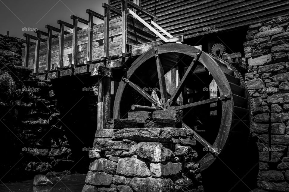 Black and white of the waterwheel and flume at the old watermill or gristmill at Historic Yates Mill County Park in Raleigh North Carolina, Triangle area, Wake County.