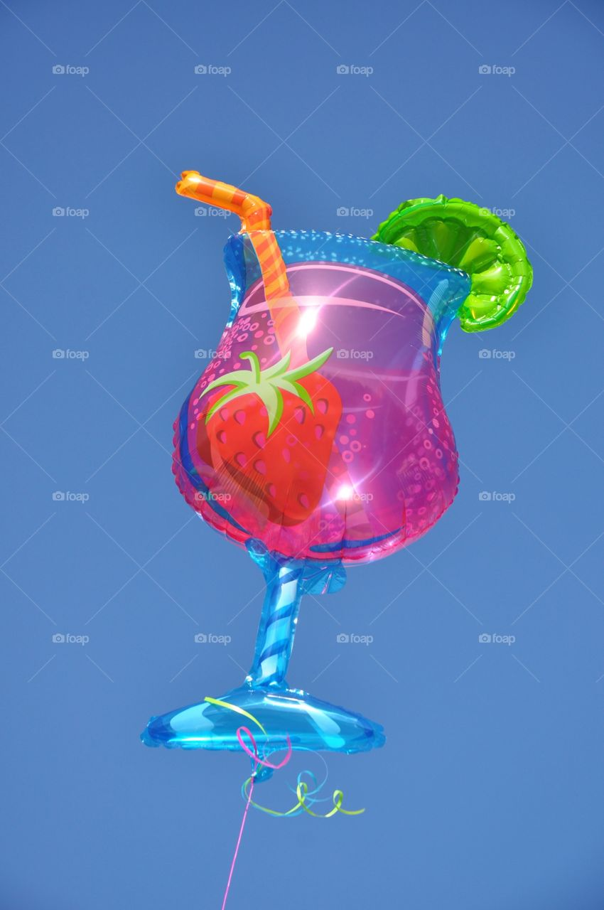 Tropical drink balloon floats against a bright blue sky.
