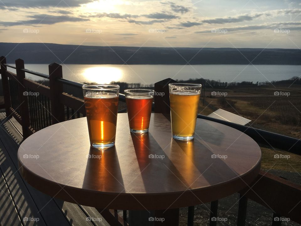 Beer glasses on table at lake side during sunset