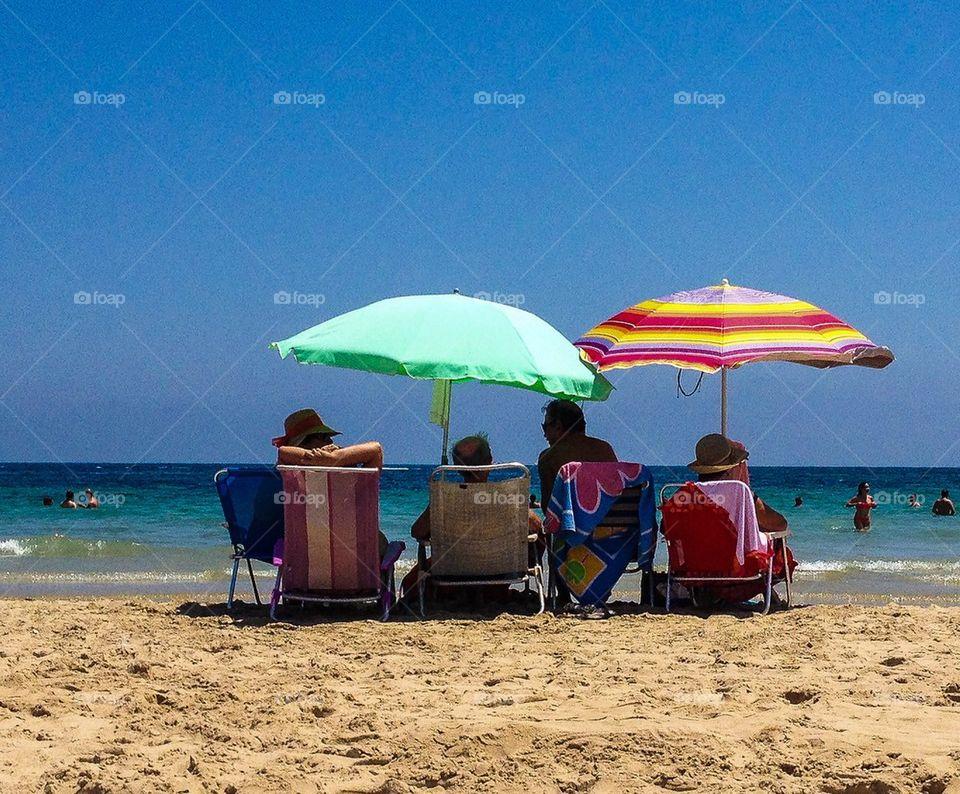 Summer vacation . People sitting under umbrellas on a sandy beach
