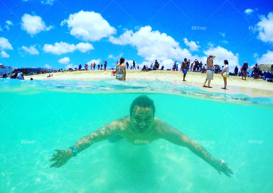 Swimming in the clear blue water by Maho Beach,  St Maarten