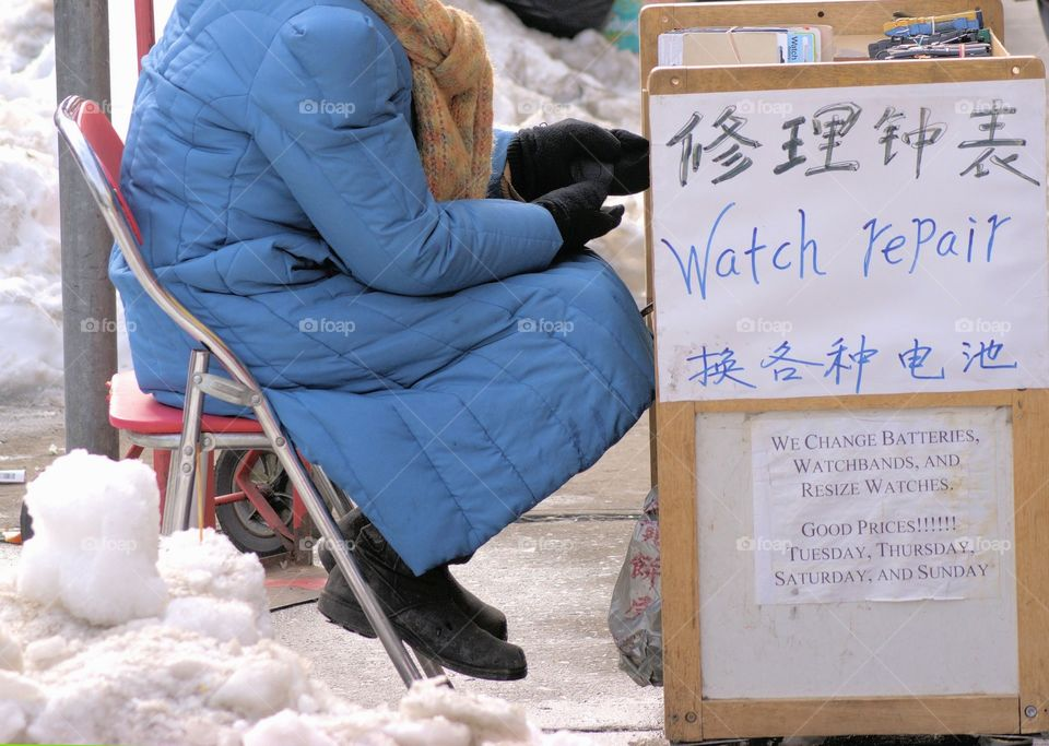 Person sitting on chair for selling watchband and batteries