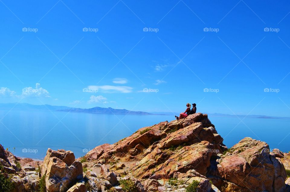 Couple sitting on rocky mountain at sea side