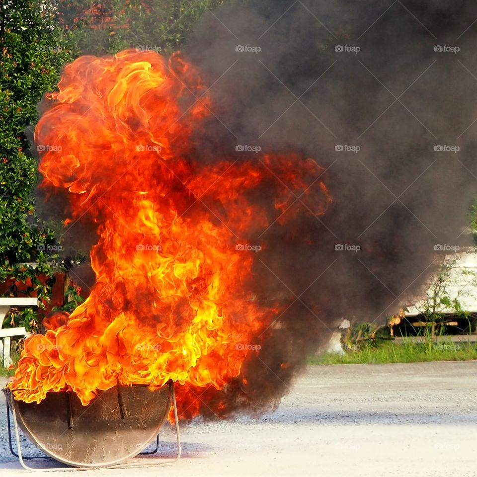 Controlled explosion which created a red flame inside a cut-in-half metal container.