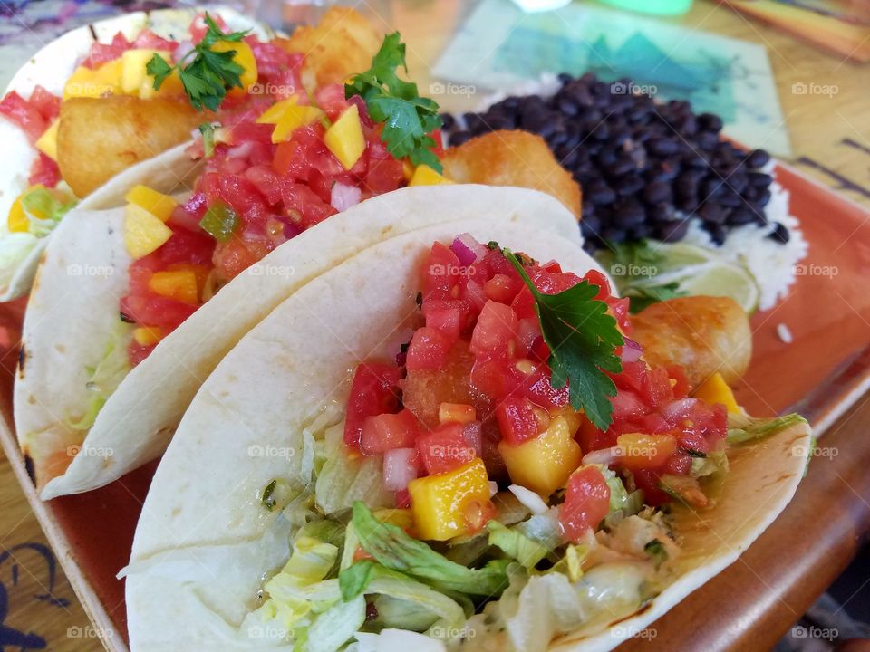 Fish tacos on flour tortilla topped with mango salsa with a side of white rice and black beans.