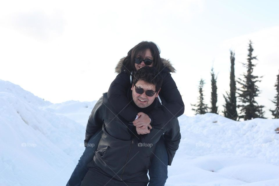 Man giving wife piggyback ride in the snowy mountain