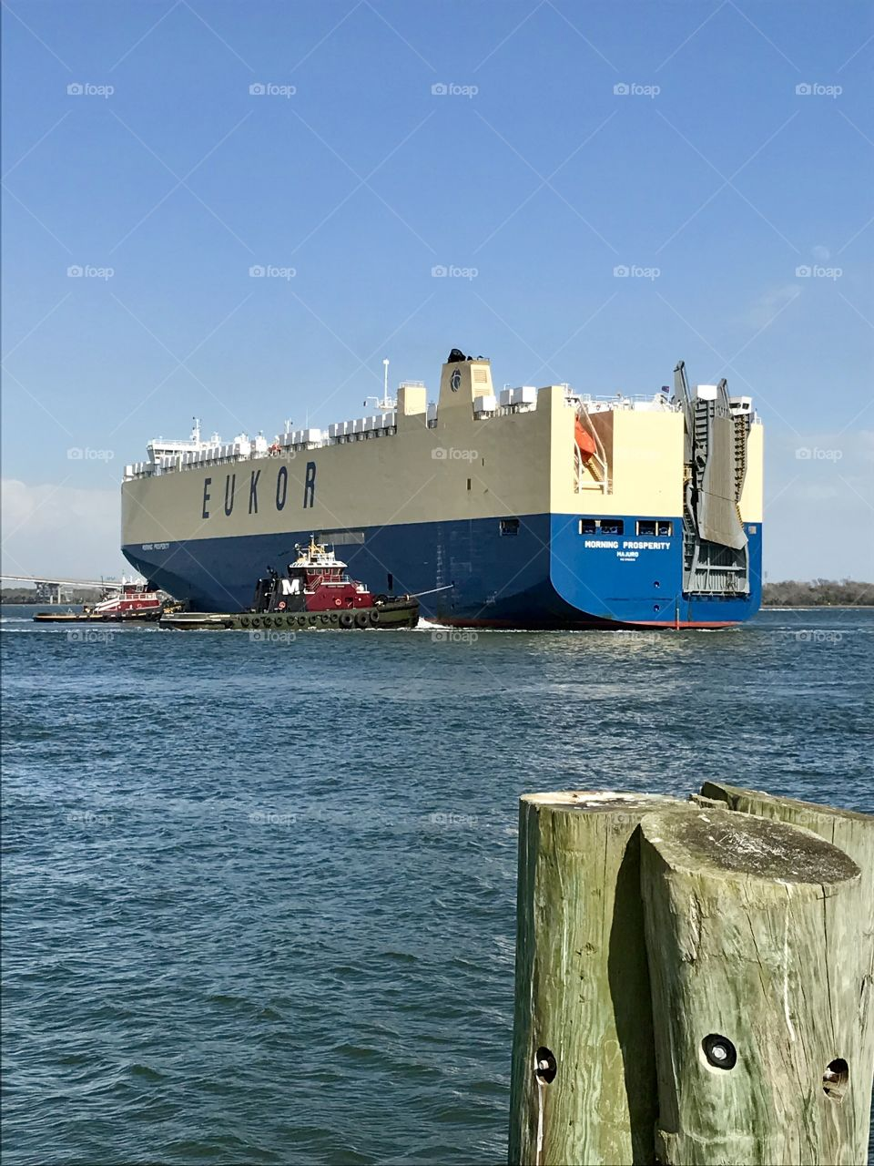 Tug boats bringing Car carrier ship into port in Charleston Harbor
