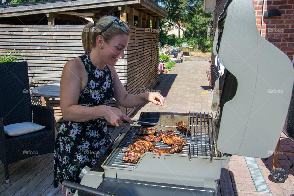 Woman working the barbecue in the summer in Höllviken in Sweden.