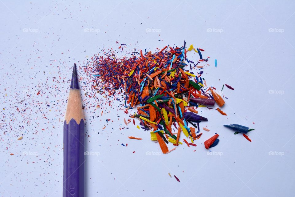 Colour pencil with pencil shavings against white background