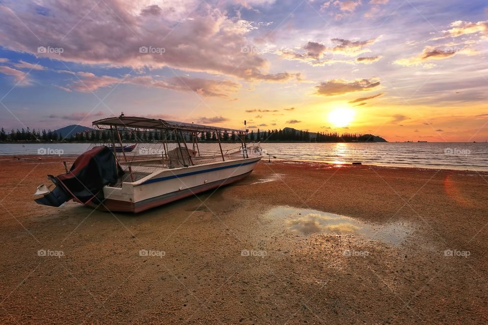 Fisherman boat at the beach with sunset background
