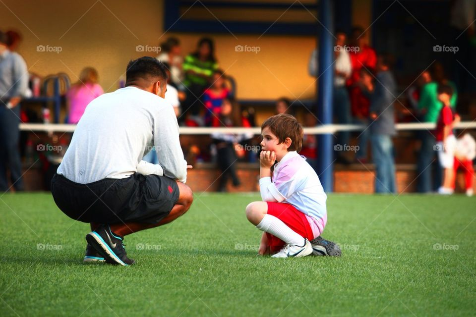 Football coach giving instructions to young kid player