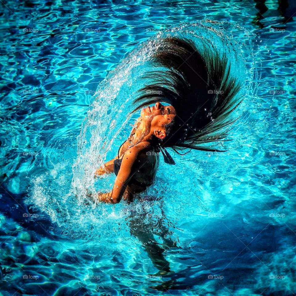 Woman splashing water with her hairs in pool