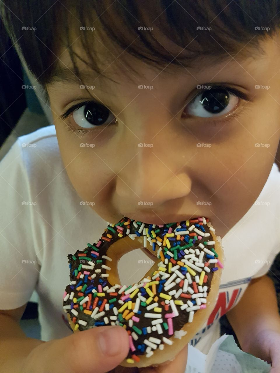 kid eating donut looking at camera