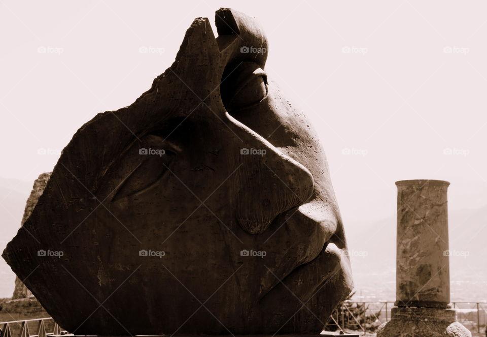 mitoraj face sculpture near a pompeian column