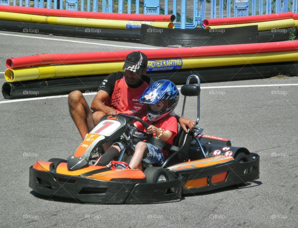 Young learner. Young kid learning to drive a go-kart
