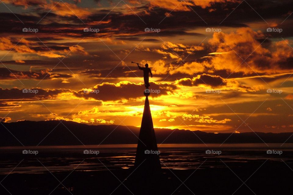 The Angel Moroni Statue atop the Bountiful LDS Temple in Bountiful Utah with against a firey sunset through the clouds