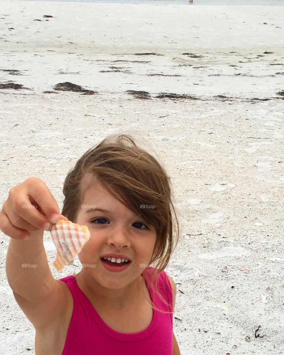 Girl holding sea shell in hand