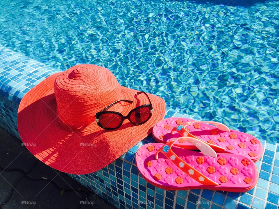 Red summer hat,pink flip flops and black sunglasses near the pool