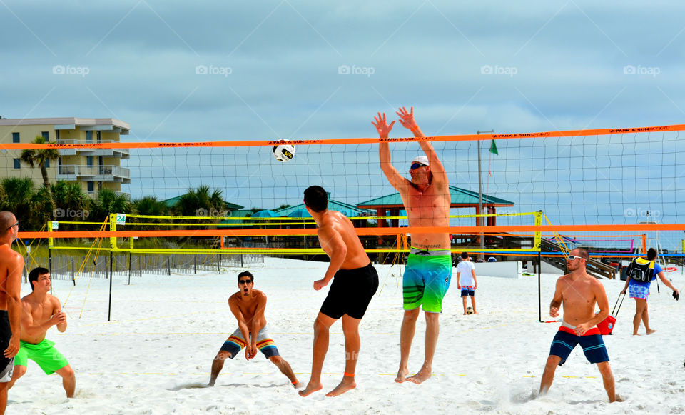 Visitors and locals play a game of pickup volleyball on the beach in front of the Gulf of Mexico!