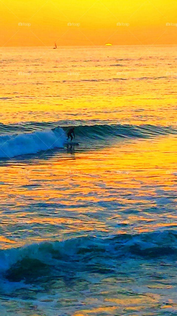 Surfer @ Sunset. Surfer enjoing the waves @ beautiful orange sunset in Laguna Beach.