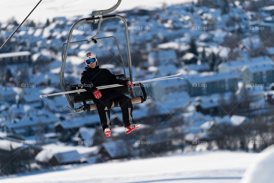 Ski jumper in lift to the top