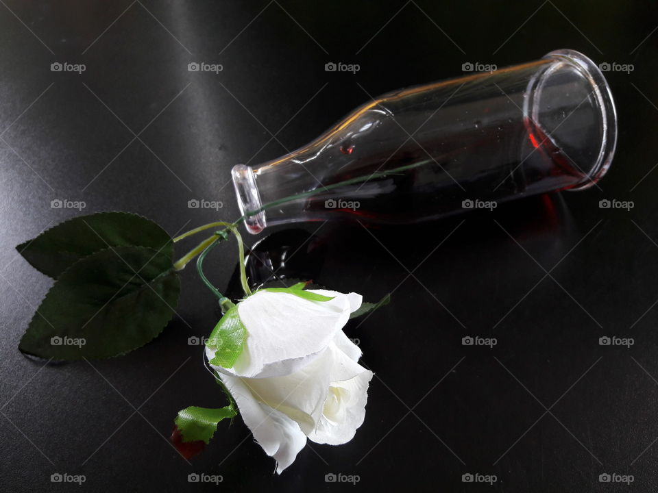 Fake rose flower with glass bottle