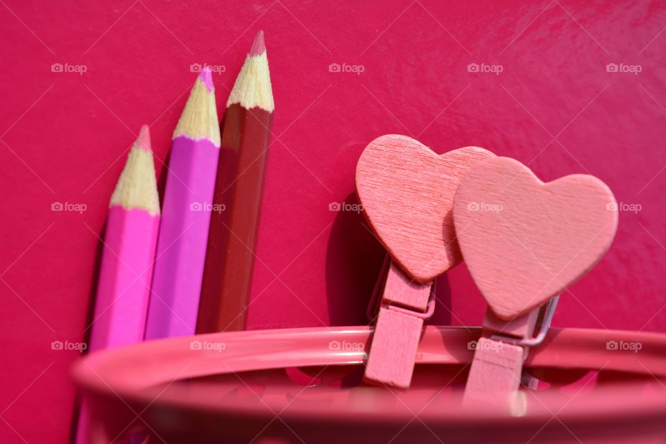 pink color wooden pencils and wood hearts pink background
