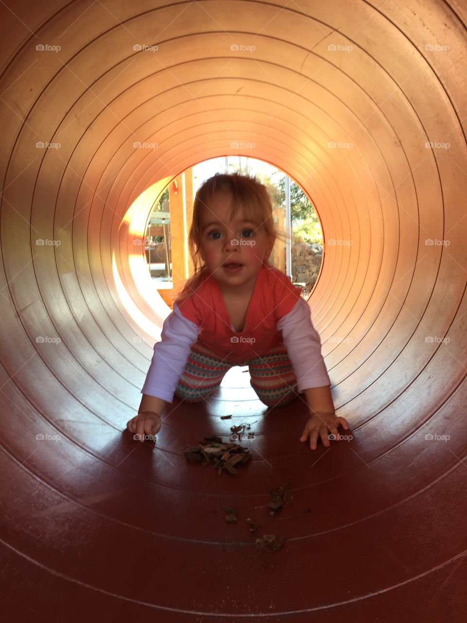 Small girl playing in tunnel
