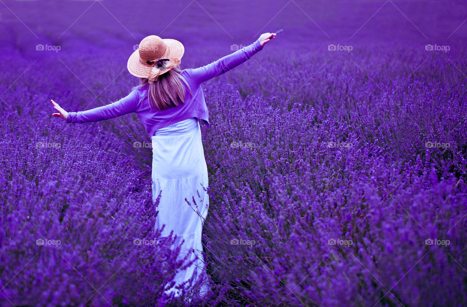 Back view of young blond woman in lavender field. Happy and carefree female in a white dress and straw hat enjoying nature. Outdoors portrait.