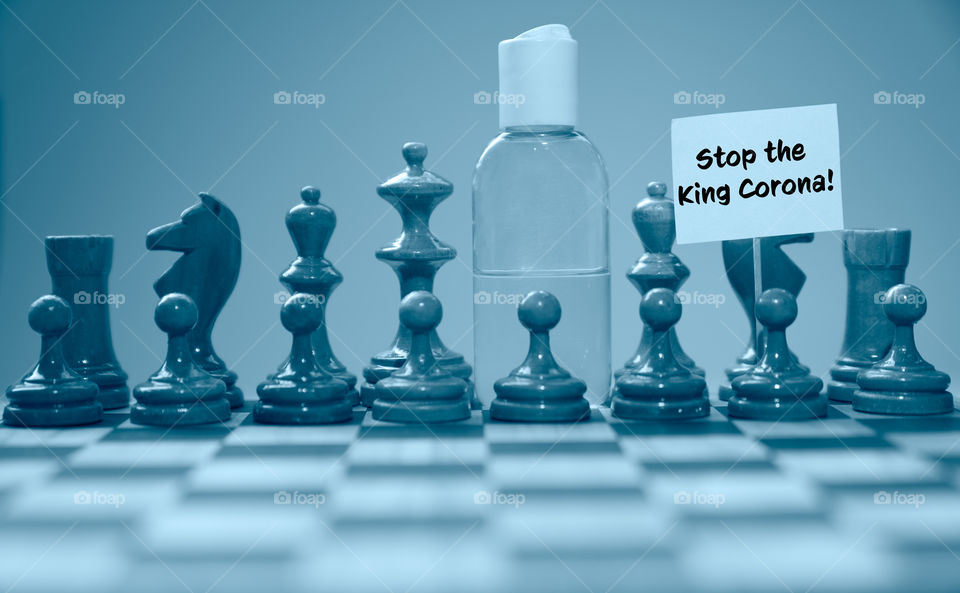 Coronavirus concept image chess pieces and hand sanitizer on chessboard illustrating global struggle against novel covid-19 outbreak.