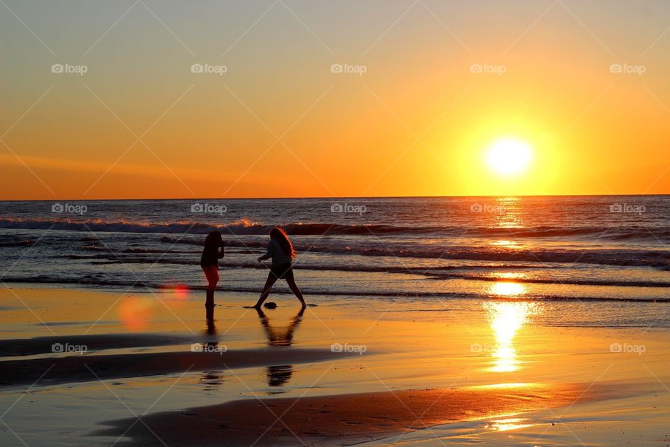 The silhouette of two children playing in the shoreline at dawn.