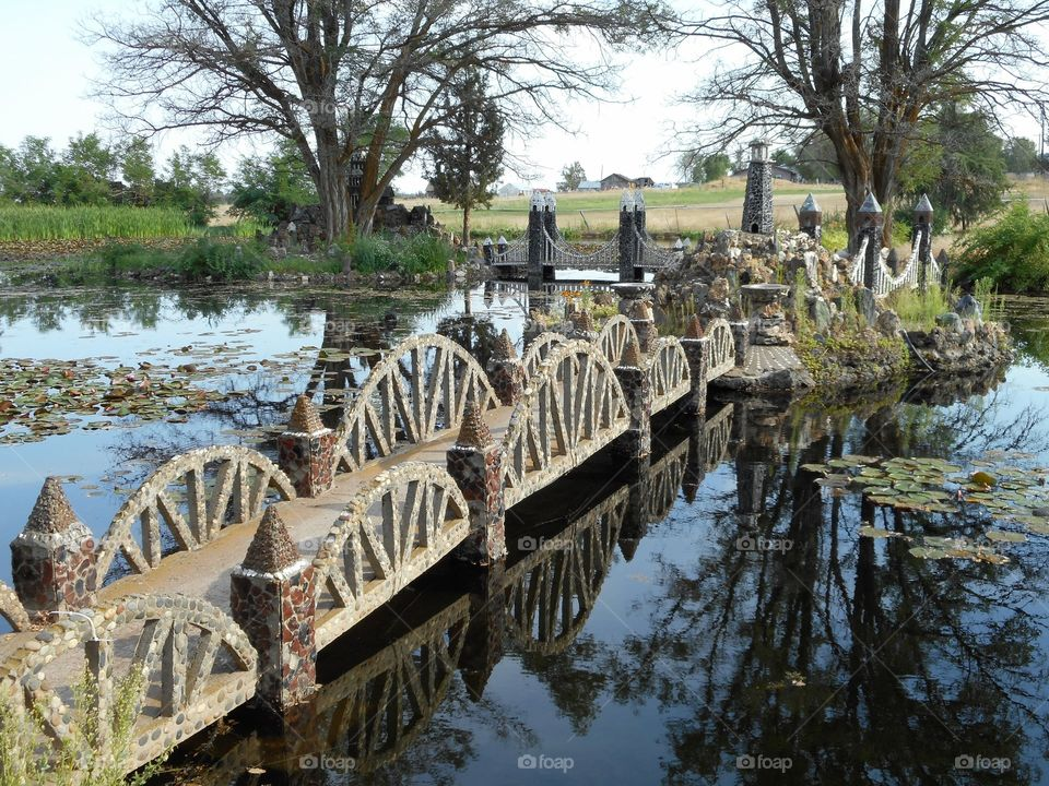 A decorative and detailed rock foot bridge crosses a pond to a center island on a summer day in Central Oregon.