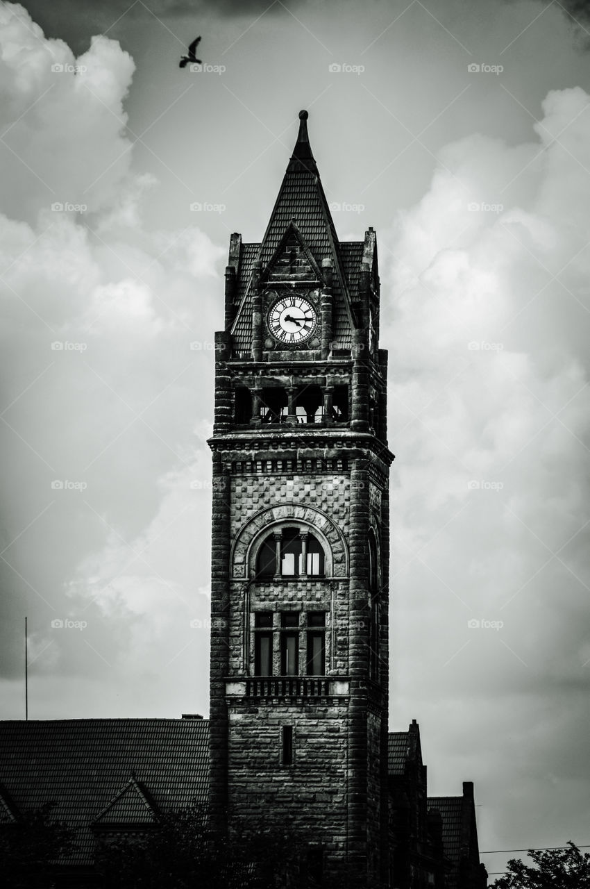 Antique chapel. Bay City, MI-June 8, 2015: Though this antique chapel is no longer running, then only thing working is the clock. It really stamds out amongst the town. The black and white filter not only gives it an eerie look, but emphasizes the age.