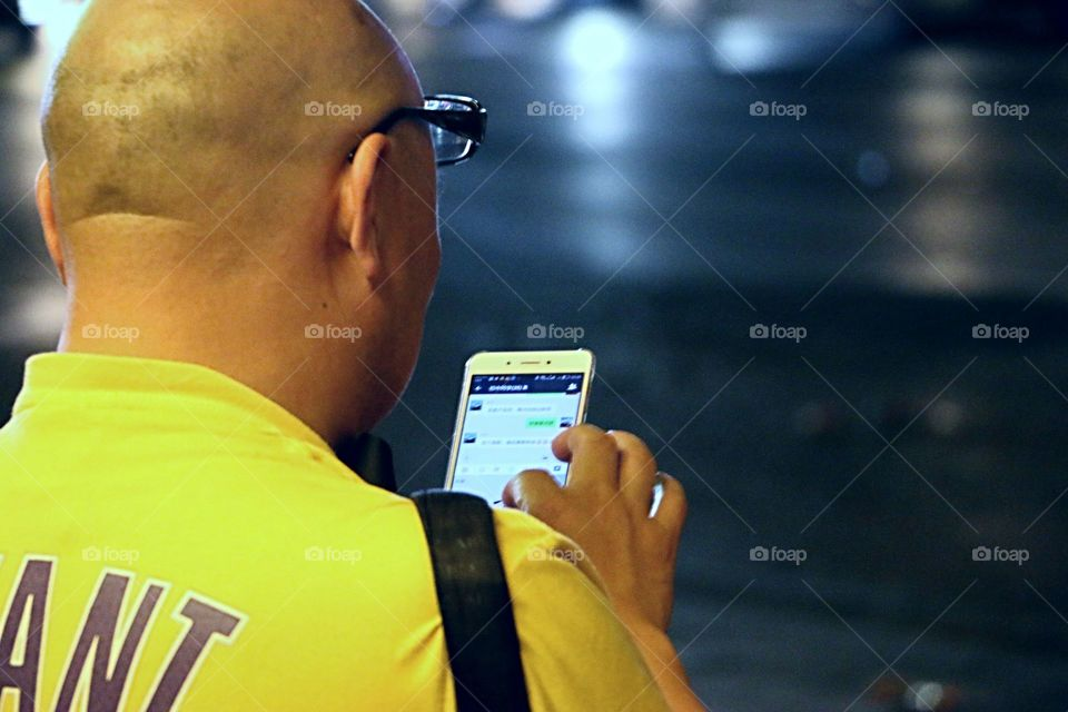 Image of bald man with glasses on his head  using his cellphone